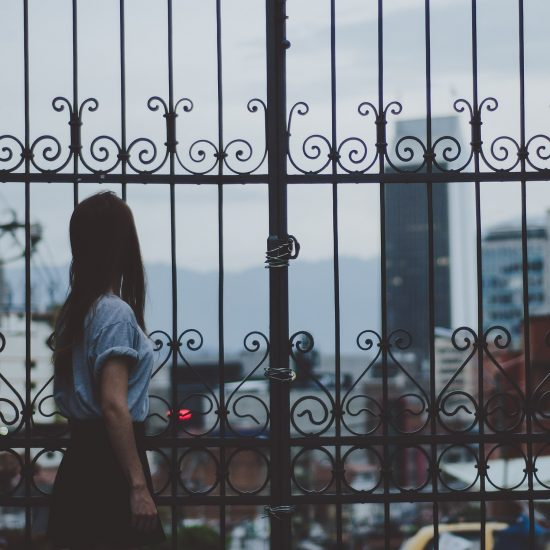 Woman looking through tall gate.