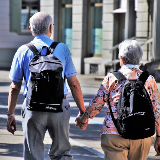 Two older adults holding hands and wearing backpacks.