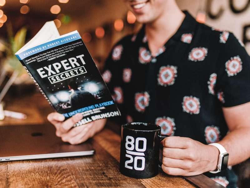 Man reading book on expert secrets in a restaurant with coffee mug