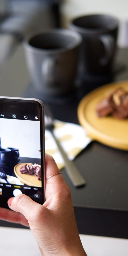 Person snapping photo of restaurant food to share on social
