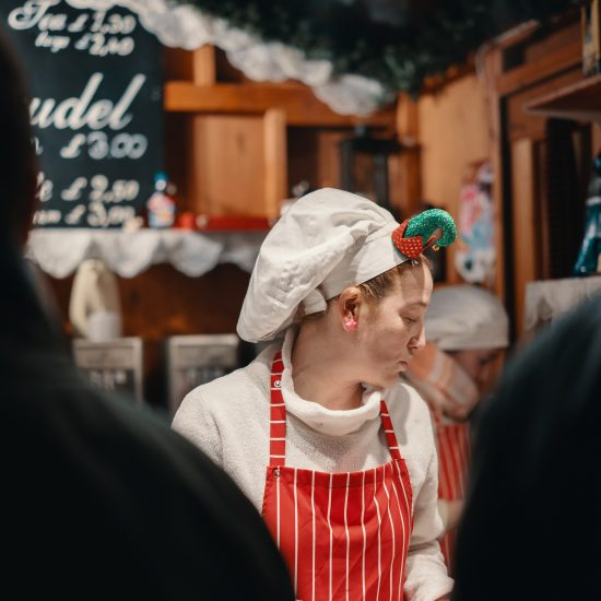Restaurant worker wearing elf chef hat and red apron